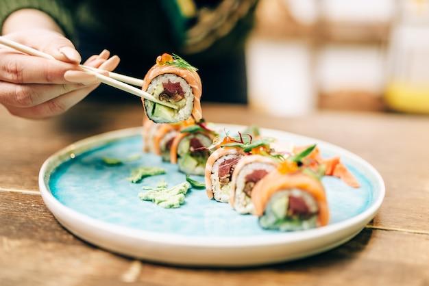 Mannelijke persoon eet sushibroodjes met stokjes