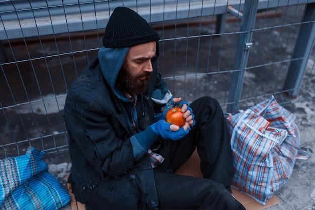 Mannelijke persoon geeft voedsel aan bebaarde vuile bedelaar op straat in de stad.