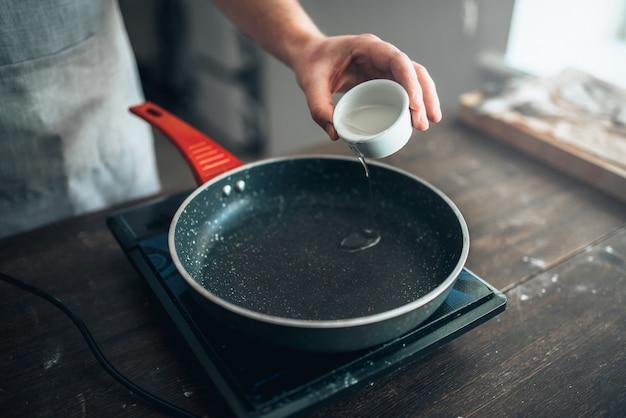 Mannelijke persoon handen gieten olie in een koekenpan. eten koken