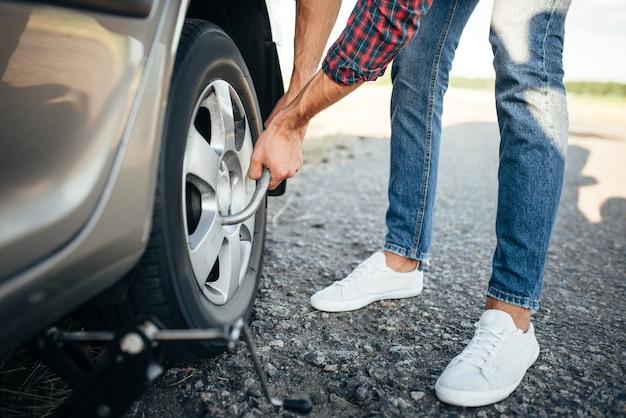 Mannelijke persoon handen met wielmoersleutel, gebroken auto. voertuig met lekke band langs de weg
