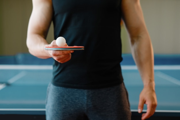 Mannelijke persoon houdt racket en pingpongbal erop, traint binnenshuis. man in sportkleding op training in tafeltennisclub