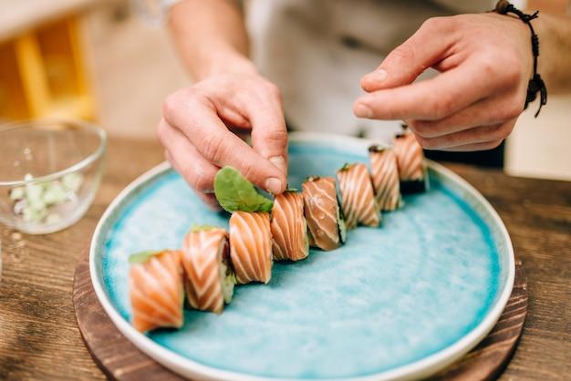 Mannelijke persoon koken sushi rolt met zalm op houten tafel