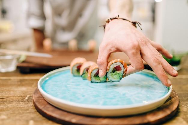 Mannelijke persoon koken sushi rolt op houten tafel, japanse keuken voorbereidingsproces.