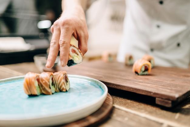 Mannelijke persoon koken sushi rolt op houten tafel