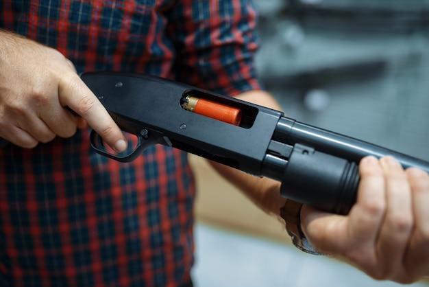 Mannelijke persoon laadt geweer bij showcase in wapenwinkel