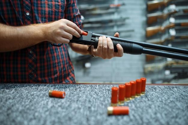 Mannelijke persoon met geweer laadt munitie bij showcase in wapenwinkel gun