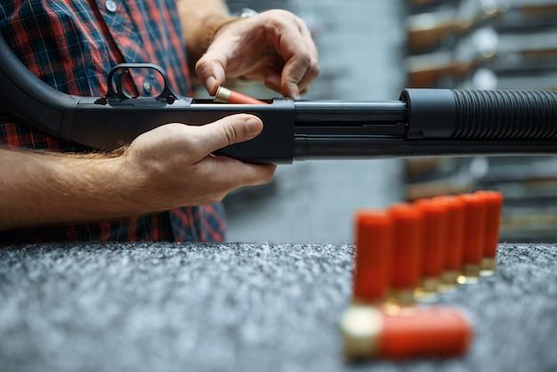 Mannelijke persoon met geweer laadt munitie op showcase in wapenwinkel.