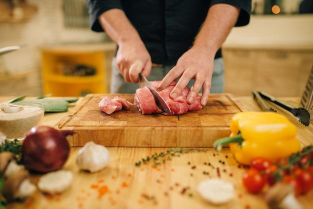 Mannelijke persoon met mes snijdt rauw vlees in plakjes, close-up
