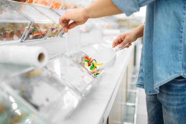 Mannelijke persoon pakt pakket zoete taaie snoepjes op