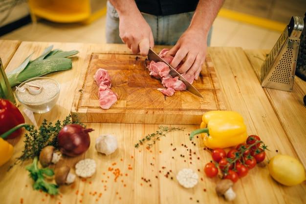Mannelijke persoon snijdt rauw vlees in plakjes, bovenaanzicht
