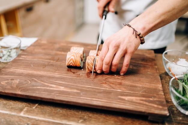 Mannelijke persoon sushi koken op houten tafel, japans voedselbereidingsproces.