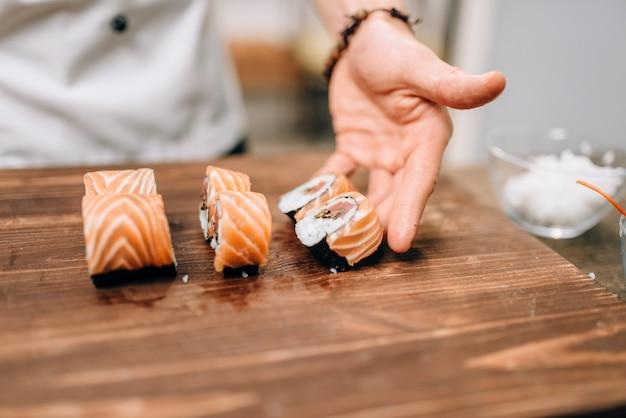Mannelijke persoon sushi koken op houten tafel, japanse keuken voorbereidingsproces.