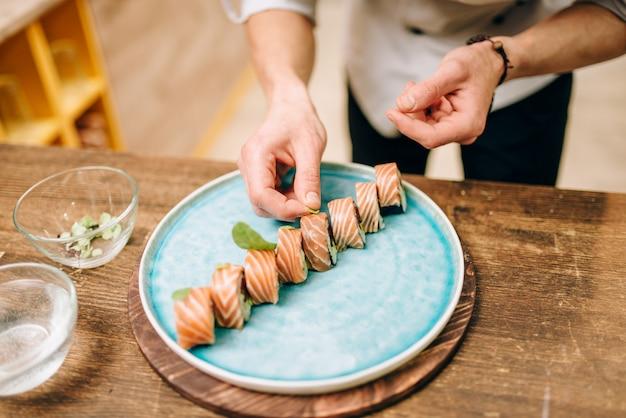 Mannelijke persoon sushi rollen, japans eten koken
