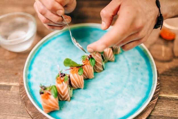 Mannelijke persoon sushi rollen met zalm koken