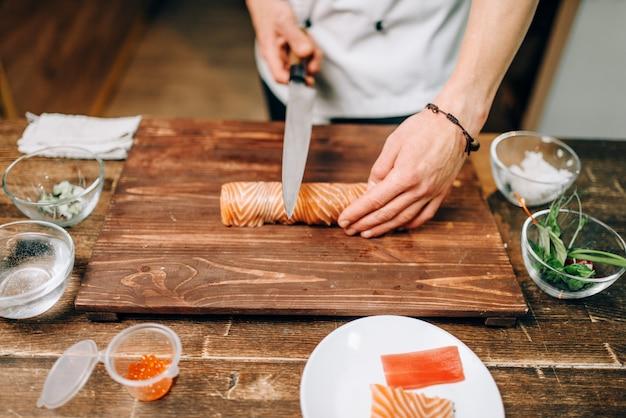 Mannelijke persoon zeevruchten koken op houten tafel, japans voedselbereidingsproces.