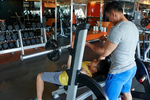 Mannelijke persoonlijke trainer die aziatische cliënt op de pers van de barbellbank in gymnastiek instrueren
