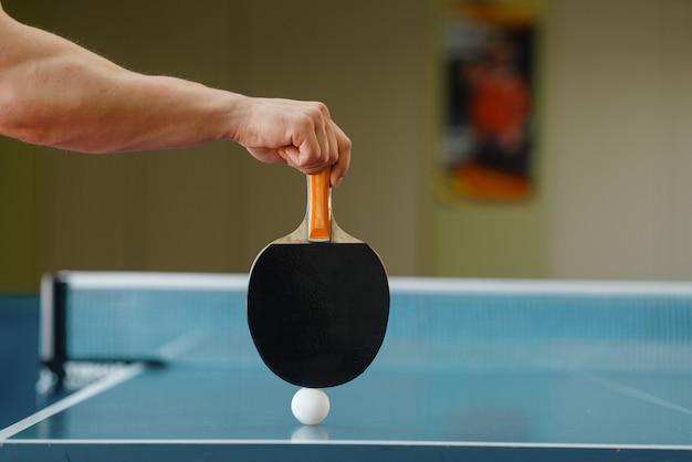 Mannelijke persoonshand met racket en pingpongbal op tafel, training binnenshuis. man op training in tafeltennisclub