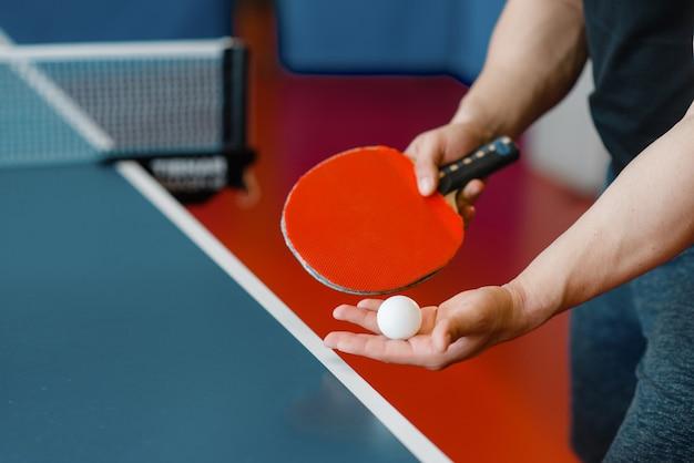 Mannelijke persoonshanden met pingpongracket en bal, training binnenshuis. man in sportkleding aan tafel met net, trainen in tafeltennisclub in