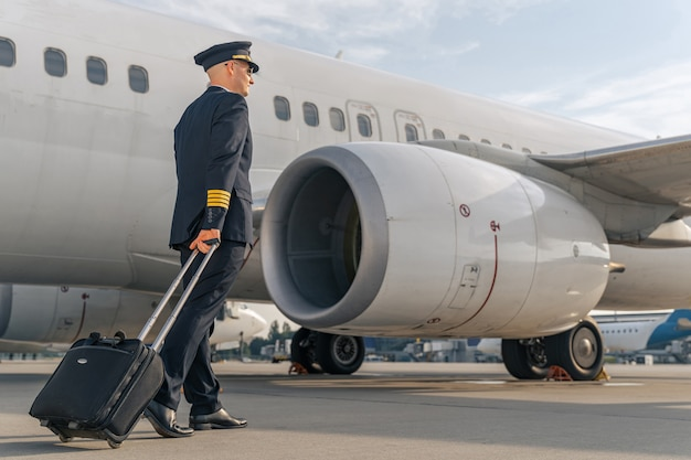 Mannelijke piloot die buiten langs commercieel vliegtuig loopt