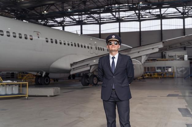 Mannelijke piloot in een zwart pak staat in een hangar
