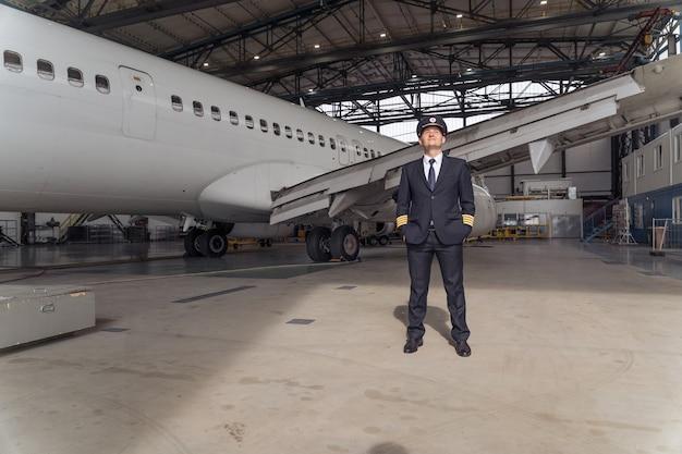 Mannelijke piloot poseren tegen de achtergrond van het vliegtuig in de hangar