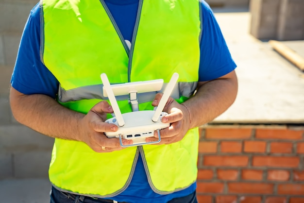 Mannelijke piloot vliegende drone quadcopter staande met afstandsbediening buitenshuis