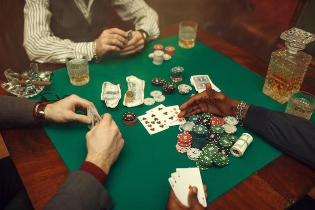 Mannelijke pokerspelers aan speeltafel met groene doek
