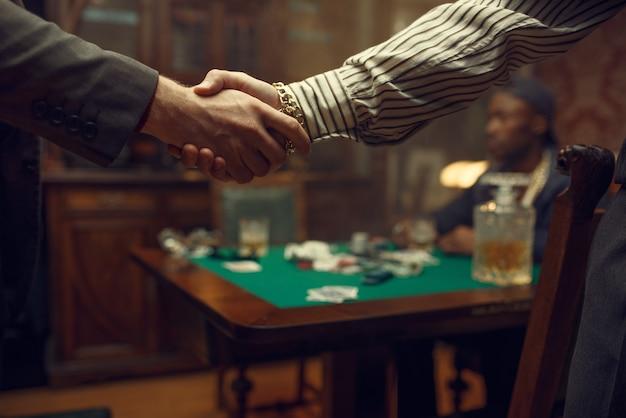 Mannelijke pokerspelers schudden elkaar de hand in het casino. verslaving, risico, gokhuis