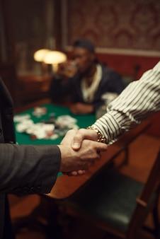 Mannelijke pokerspelers schudden handen in casino