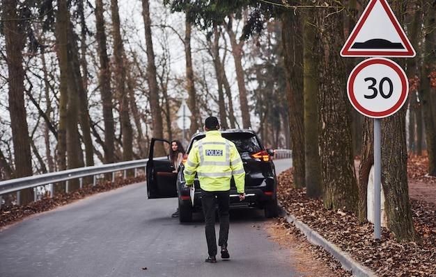 Mannelijke politieagent in groen uniform lopen naar het voertuig op de weg.