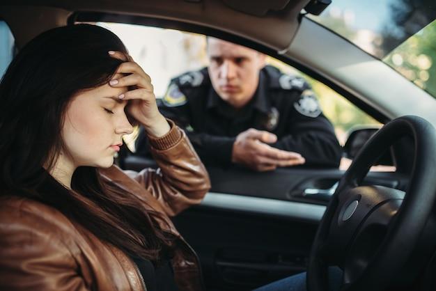 Mannelijke politieagent in uniform check vrouwelijke chauffeur op weg
