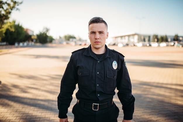 Mannelijke politieagent in uniform op de weg