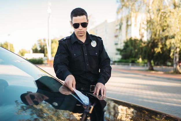 Mannelijke politieagent in uniform schrijft een boete op de weg