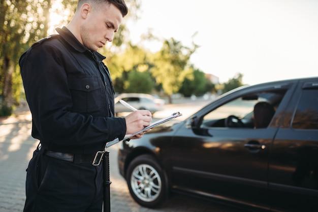 Mannelijke politieagenten schrijven onderweg een boete uit