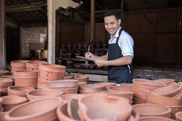 Mannelijke pottenbakker die van zijn aardewerkproduct controleert