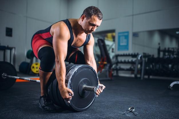 Mannelijke powerlifter bereidt een halter in de sportschool