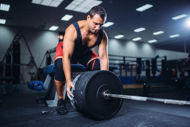 Mannelijke powerlifter bereidt een halter voor deadlift in sportschool.