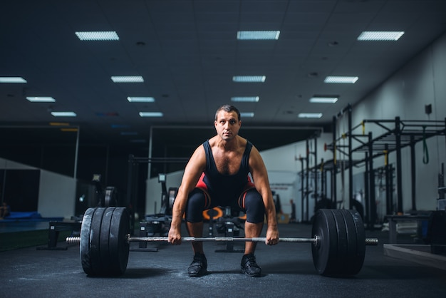 Mannelijke powerlifter deadlift barbell in sportschool beginnen