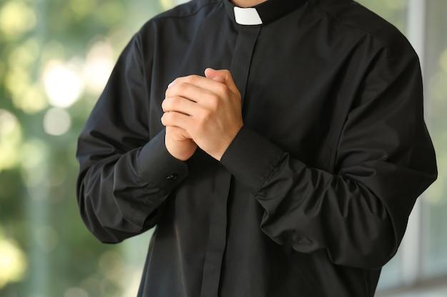 Mannelijke priester die thuis bidt Premium Foto