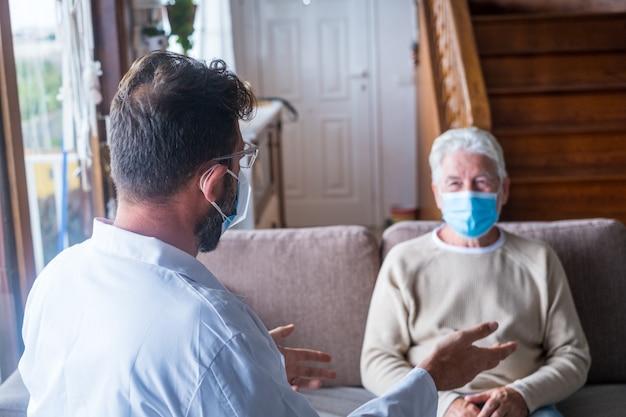Mannelijke professionele arts die een oudere patiënt raadpleegt tijdens een bezoek aan de medische zorg met maskers