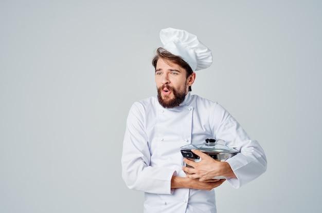 Mannelijke professionele chef-kok met een pan in zijn handen die voedselrestaurant voorbereidt