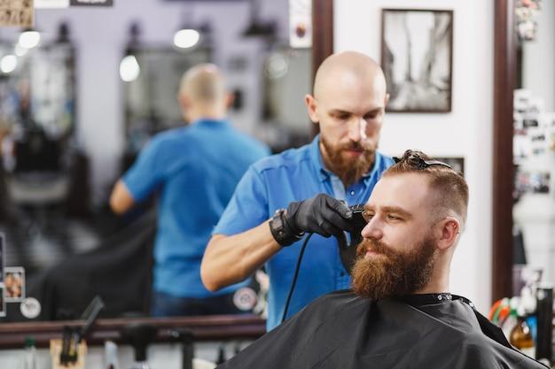 Mannelijke professionele kapper die cliënt door clipper bedient