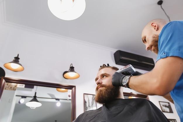 Mannelijke professionele kapper die cliënt door clipper bedient Gratis Foto