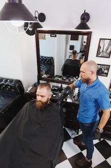 Mannelijke professionele kapper die cliënt door föhn bedient