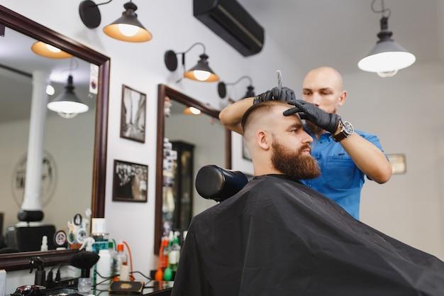 Mannelijke professionele kapper die klant bedient, scheermes met dikke baard scheren