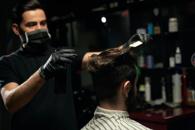 Mannelijke professionele kapper gekleed in zwart shirt, masker dragen op mond en handschoenen aan handen doet haarstyling aan ongeschoren man die bedekt is met gestreepte cape zittend in fauteuil bij barbershop