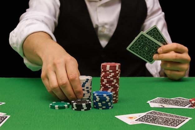 Mannelijke professionele pokerspeler die een weddenschap plaatst om het pokerspel te spelen in een casino met groen laken en zwart. verpest concept, online winnaar