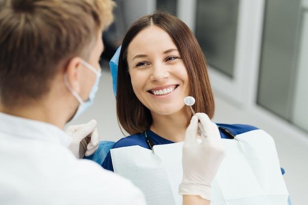 Mannelijke professionele tandarts met handschoenen en masker en bespreken hoe de behandeling eruit zal zien van de tanden van de patiënt