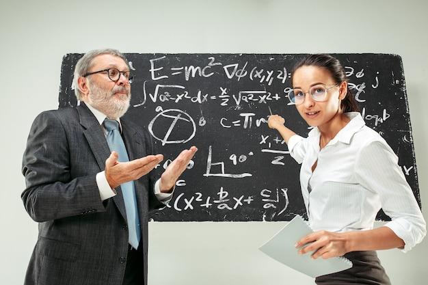 Mannelijke professor en jonge vrouw tegen schoolbord in de klas