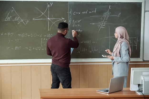 Mannelijke professor en jonge vrouwelijke student in hijab die bij het bord staan en de vergelijking oplossen tijdens de les terwijl de man naar een van de derivaten wijst